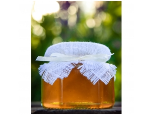 Honey jar decorated with white linen and ribbon